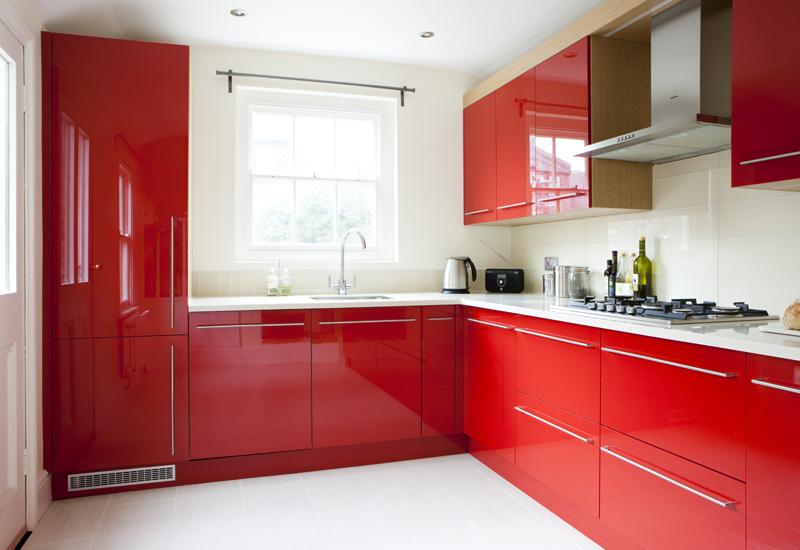 современный дизайн кухни с угловым фасадом красного цвета